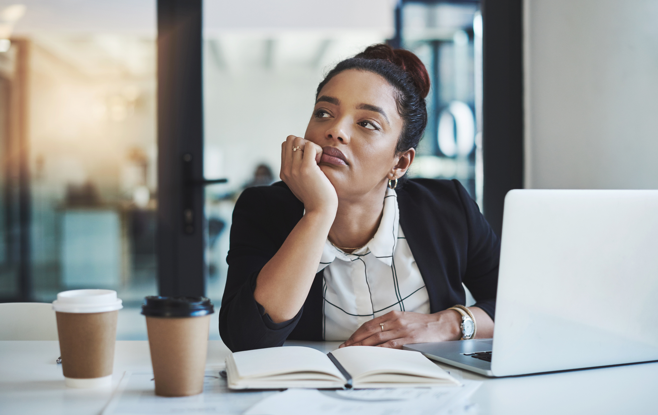 Shot of a young businesswoman looking bored while working at her desk in a modern office