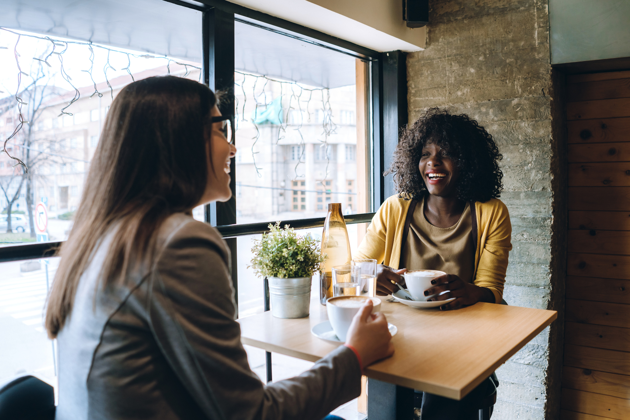 Multiethnic female friends are chatting and drinking coffee in downtown café